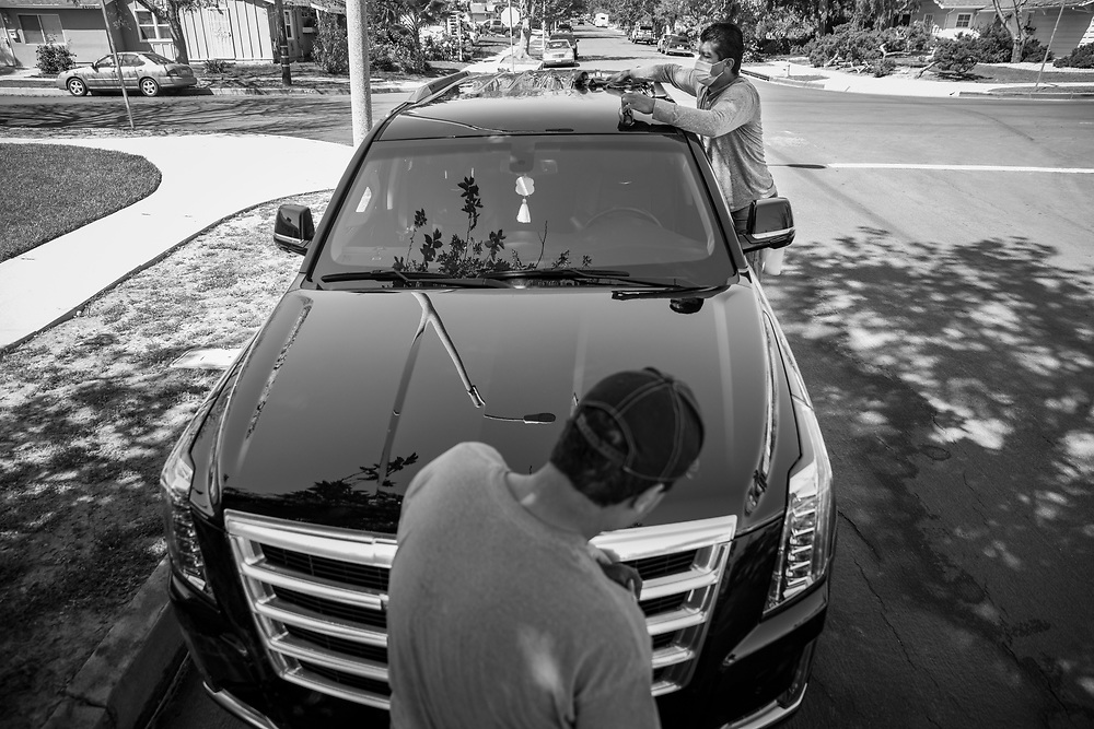 A mobile car wash business, listed as a non-essential business by the city of Los Angeles and therefore operating illegally,  finishes a car on the streets of Los Angeles.