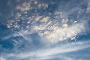 Cloud puffs dot blue sky near sunset in Canada.