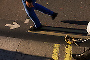 Pedestrians avoid a squashed banana skin that lies in the gutter of a London street.