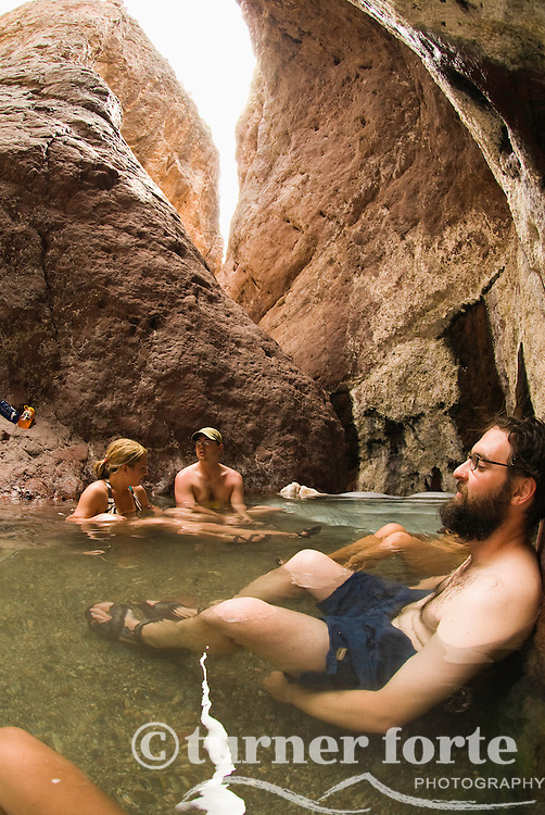 Friends relax in the Arizona Hot Springs after an eight hour paddle up the Colorado River, Black Canyon, Nevada.