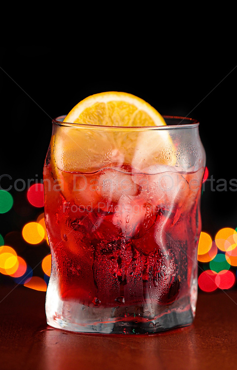 Bitter aperitif in a glass with ice and a slice of orange with colorful defocused lights on the background.