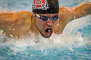 Chris Kaiser-Nyman '13 breaks out of the water during the Men's 100 yard Butterfly at the Grinnell College Pioneer Invitational.<br /> BEN BREWER/Grinnell College