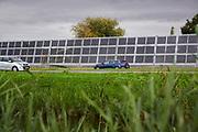 Solar panels on a noise barrier along a motorway. | Zonnepanelen op een geluidsscherm langs een autoweg.