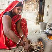 CAPTION: In the courtyard outside her home, Seema Devi uses dried grass to light a fire in her traditional earthen stove. LOCATION: Singhilpur, Saran District, Bihar, India. INDIVIDUAL(S) PHOTOGRAPHED: Seema Devi.