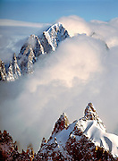 Clouds swirl around the jagged spires of the Aiguilles du Midi, above Chamonix, in the Mount Blanc Massif of France.