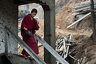 Monk runs down the stairs with a rice bowl before food is served during all-day prayer in Kurje Lhakhang.