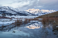 Sunrise over Deer Creek Reservoir as Mount Timpanogos shines and reflects in the calm waters of an early Winter morning.