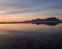 Midnight sun mountain reflection on Ytresand beach, Moskenesøy, Lofoten Islands, Norway