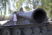 Israel, Upper Galilee, Metula, (founded 1896) is situated on the Lebanese boarder. Children play on an old tank left as a memorial for the protectors of Metula. Model Release available