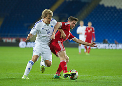 CARDIFF, WALES - Saturday, November 16, 2013: Wales' Joe Allen in action against Finland's Teemu Pukki during the International Friendly match at the Cardiff City Stadium. (Pic by David Rawcliffe/Propaganda)