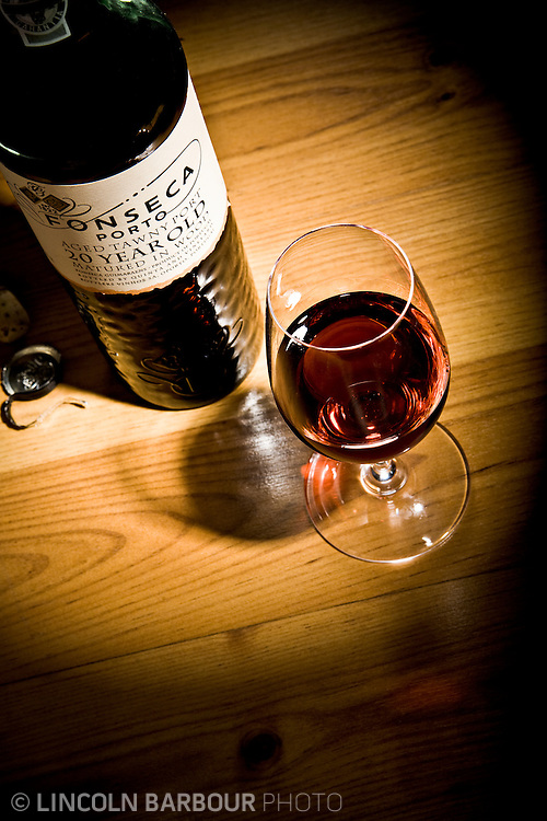 A bottle and glass of Fonseca Porto 20 Year spotlighted on a wood table.