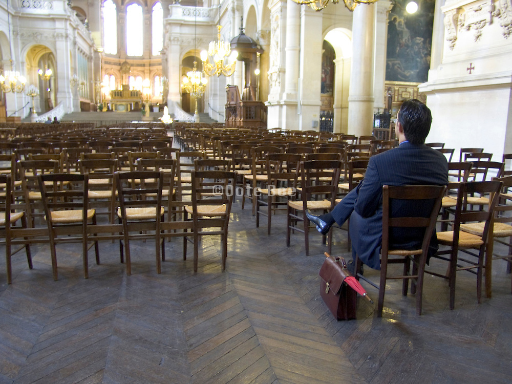 business man by himself praying in a church France Paris
