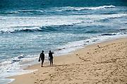 A Couple Walking Along the Shore of Manhattan Beach