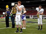 26 Nov. 2010 -- ST. LOUIS -- Mound City High School football players Elijah Poe (51, center) and Dayne Messer (80, right) join cheerleader Lilly Grant (center) and other members of the Mound City band in their half-time performance during the MSHSAA 8-man football championship game at the Edward Jones Dome Friday, Nov. 26, 2010. Mound City, located in Holt County, has a total enrollment of 89 students in grade nine through twelve. Image © copyright 2010 Sid Hastings.