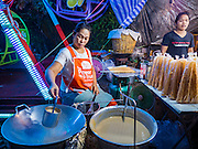 21 NOVEMBER 2015 - BANGKOK, THAILAND: A vendor makes a snack at the Wat Saket temple fair. Wat Saket is on a man-made hill in the historic section of Bangkok. The temple has golden spire that is 260 feet high which was the highest point in Bangkok for more than 100 years. The temple construction began in the 1800s in the reign of King Rama III and was completed in the reign of King Rama IV. The annual temple fair is held on the 12th lunar month, for nine days around the November full moon. During the fair a red cloth (reminiscent of a monk's robe) is placed around the Golden Mount while the temple grounds hosts Thai traditional theatre, food stalls and traditional shows.     PHOTO BY JACK KURTZ