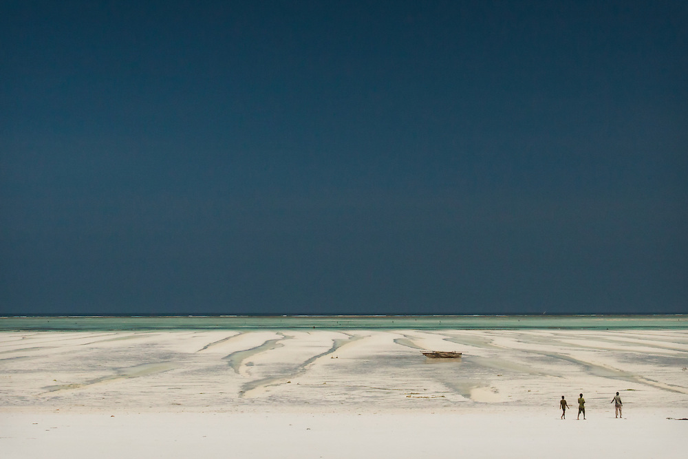 Three men on Pongwe Beach, along the northeast coast of Zanzibar, during low tide. A barrier reef one kilometre from the shore is responsible for the fine white sand and clear turquoise water.