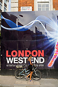 A woman pushes a bicycle past a poster advertising London's affluent West End. London, UK