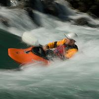 Kayaker Jeff Germaine plays in waves on the  Kananaskis River in the Canadian Rockies near Calgary, Alberta