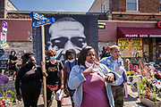 "15 AUGUST 2020 - MINNEAPOLIS, MINNESOTA: Women in front of the George Floyd Memorial in Minneapolis. Floyd, an unarmed Black man, was killed by Minneapolis police officers of May 25 in front of Cup Foods, a convenience store at the intersection of 38th and Chicago Ave. His killing sparked a week of violent protests across the country. The intersection where he was killed is still closed and has become an unofficial memorial visited by hundreds of people every day. Saturday, more than 100 people gathered at the memorial to demand the city preserve the memorial. On Saturdays in August, the intersection has a market, with venders selling Afro-centric merchandise. The city of Minneapolis had planned to start reopening the intersection as soon as Monday Aug. 17, but delayed those plans indefinitely on Friday, Aug. 14. City residents have created a ""George Floyd Zone"" at the intersection. They're demanding the recall of Hennepin County Attorney Mike Freeman, requiring Minneapolis police officers have their own private liability insurance, and the allocation of funds for businesses and residents in the community. The city is considering officially renaming Chicago Ave. between 37th and 39th ""George Floyd Jr. Place.""     PHOTO BY JACK KURTZ"