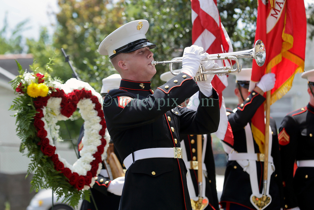 29 August 2015. Lower 9th Ward, New Orleans, Louisiana.<br /> Hurricane Katrina 10th anniversary memorials.  <br /> A Marine plays Taps in memory of all those who perished in the storm. <br /> Photo credit©; Charlie Varley/varleypix.com.