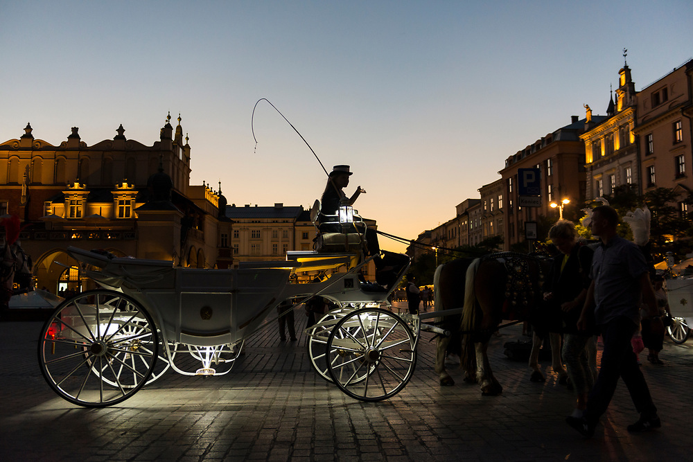 Krakow, Poland - August 26, 2016: A Polish woman sits in her horse-drawn carriage in Krakow's Rynek Glowny square at dusk, waiting for a fare. The carriages are popular with tourists.
