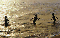Children playing in the surf at Ada, Ghana, on the coast of the Gulf of Guinea