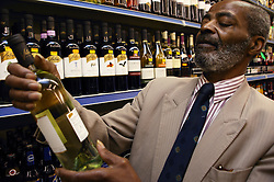 Old man selecting a bottle of white wine,
