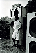 Girl wearing white Bermuda shorts, in front of speakers. Sound System Photo by Richard Saunders 1983