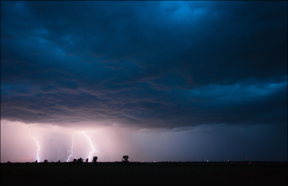 Three cloud to ground lightning strike in the far distance right after sunset during nautical twilight a few mile northwest of Salina, Kansas.