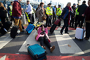 Passengers walk by as climate change protest group Extinction Rebellion stage a protest at London City Airport during day four of two weeks of planned demonstrations on 10th October, 2019 in London, Untited Kingdom. Extinction Rebellion is demanding that governments drastically cut carbon emissions.