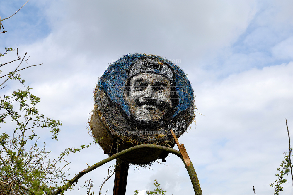 """France, April 13th 2014: A hay bale painted with the image of Gilbert Duclos Lasalle looks out over the Pont Gibus section of pave near Wallers. Duclos Lasalle won the race twice in his career (1992 and 1993) and used the section as a """"launch pad"""" for both victories."""