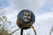 "France, April 13th 2014: A hay bale painted with the image of Gilbert Duclos Lasalle looks out over the Pont Gibus section of pave near Wallers. Duclos Lasalle won the race twice in his career (1992 and 1993) and used the section as a ""launch pad"" for both victories."