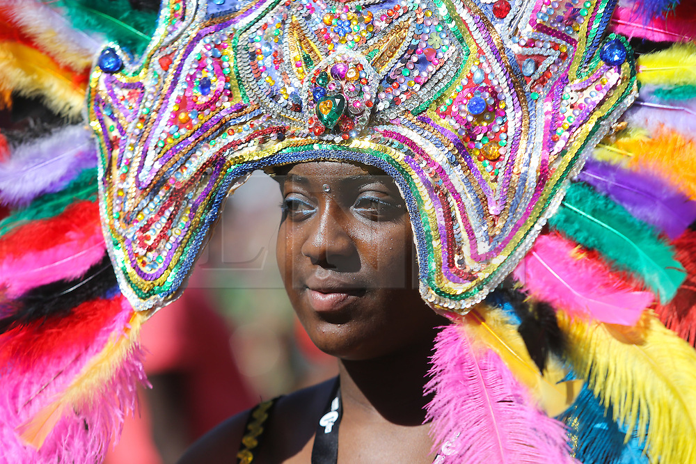 © Licensed to London News Pictures. 29/08/2016. Leeds, UK. A woman dressed in a brightly coloured feathered headdress at the Leeds West Indian Carnival in Leeds, West Yorkshire. First run in the 1960's, the Leeds West Indian Carnival is Europe's longest running authentic Caribbean carnival parade. Photo credit : Ian Hinchliffe/LNP