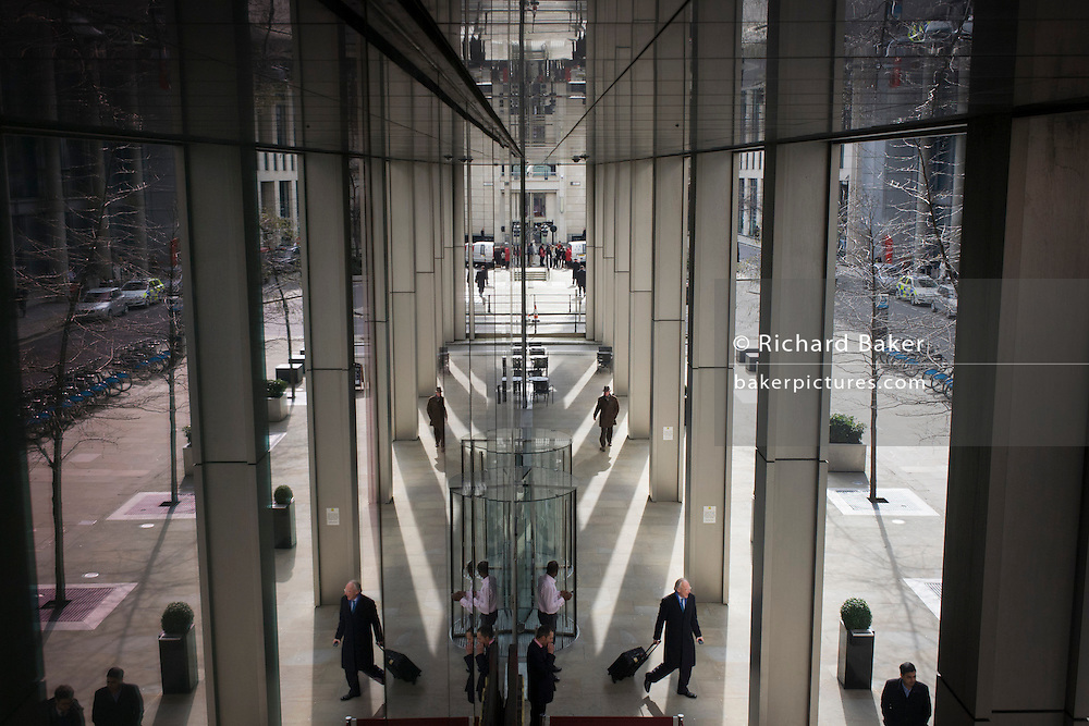 Seen from an aerial viewpoint, office workers come and go from a generic banking company. The symmetrical reflections are reproduced from a dividing line of plate glass in the capital's financial district, known as the City of London - or Square Mile. People come and go from this unidentified building entrance and exit while others stand still to smoke cigarettes under the shelter of the reflective ceiling. Shadows and light diverge towards the bottom. The City of London is the capital's historic centre first occupied by the Romans then expanded during following centuries until today, it has a resident population of under 10,000 but a daily working population of 311,000.