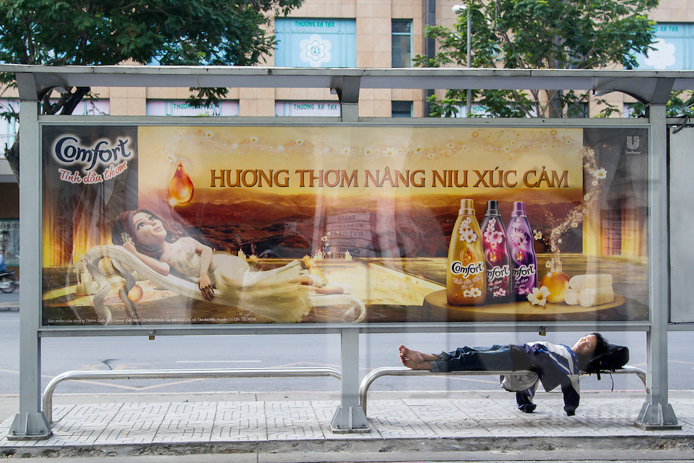Juxtaposition of young homeless man sleeping on a bus stop bench beside an advertisement with a princess lounging on a comfortable couch, Ho Chi Minh City, Vietnam, Southeast Asia