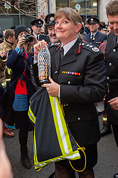 © Licensed to London News Pictures. 23/12/2019. London, UK. London Fire Brigade Commissioner Dany Cotton holds a gift bag and bottle presented by firefighters from overseas as a Guard of Honour is held in London. Firefighters from across the UK and several from overseas attended the unofficial event outside the brigades headquarters in Union Street. Commissioner Cotton is retiring in the wake of the Grenfell Fire. Photo credit: Peter Manning/LNP