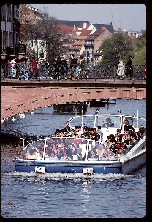 Tourist boat cruises under a sandstone bridge on the L'Ill River in April; (v) Strasbourg. France