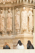 Three women sitting in front of relief sculptures of Cathedral of Notre-Dame in Reims, France