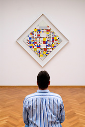 Visitor looking at abstract painting Victory Boogie Woogie by Piet Mondrian at Gemeentemuseum in Den Hague Netherlands