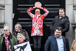 © Licensed to London News Pictures. 26/01/2019. London, UK. A protesters covered in fake blood stands at the doors to the Embassy of Japan in London during a demonstration in against Japanese whaling. Photo credit: Rob Pinney/LNP