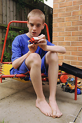 Teenage boy with autism sitting outside in garden playing with toy truck,