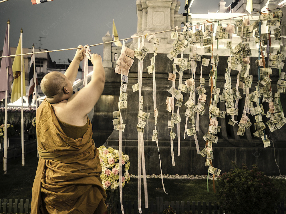Hanging money at Wat Traimit temple during the celebration of the Chinese New Year in Chinatown Bangkok Thailand. This monk is tying more ribbons to the main cord so people can keep hanging paper currency from it.