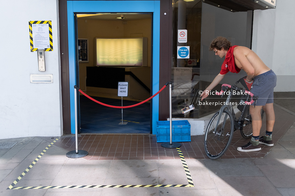 A cyclist throws a library book into a book drop-off box outside Shoe Lane Library during the Coronavirus pandemic in the City of London, the capital's financial district, on 6th August 2020, in London, England.