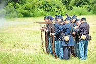 Old Bethpage, New York, USA - July 21, 2012: Musket firing at  Camp Scott, a Union Army training camp, portrayed by Federal Re-enactors at Old Bethpage Village Restoration, to commemorate 150th Anniversary of American Civil War, on Saturday, July 21, 2012, in Old Bethpage, New York, USA.