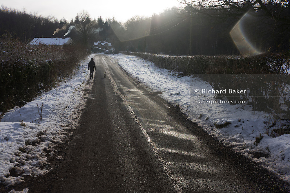 12 year-old boy walks along frozen rural road with following pet dog during wintry conditions in North Somerset.