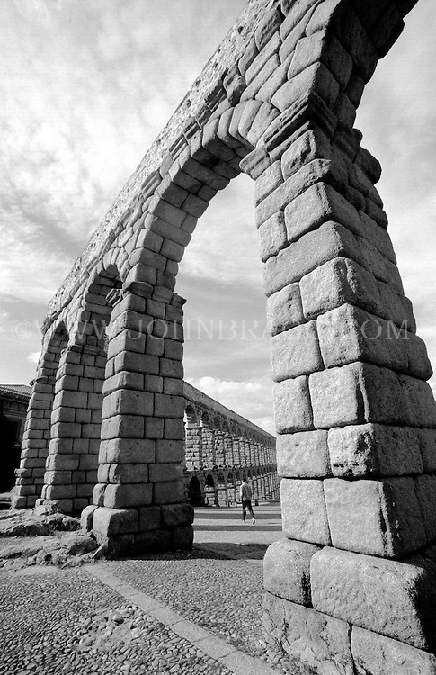 Black and white photo of an old Roman aqueduct in Segovia, Spain.