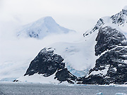 "Nicknamed ""Kodak Gap"" for its spectacular peaks above a narrow passage, Lemaire Channel lies off of Antarctica, between Kiev Peninsula in the continent's Graham Land and Booth Island. Steep cliffs hem in the iceberg-filled strait, which is 11 km long and narrows to just 1600 meters wide. Lemaire Channel was first seen by the German expedition of 1873-74, but not traversed until December 1898, when the Belgica of the de Gerlache expedition passed through. De Gerlache named it for Charles Lemaire (1863-1925), a Belgian explorer of the Congo. Popular Antarctic cruises are now attracted to Lemaire Channel by protected waters that are often as still as a lake (a rarity in the storm-wracked Southern Ocean), and the north-south traverse delivers vessels close to Petermann Island, home of the world's southernmost colony of Gentoo Penguins. The principal difficulty is that icebergs may fill the channel, especially in early season, obliging a ship to backtrack around the outside of Booth Island to reach Petermann."