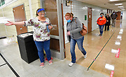 Election judge Danielle Wilburn (left) gestures for voter Collette Parsons of Belleville to enter the Douglas School gym to cast her ballot as other voters practice social distancing while standing in line on Tuesday, November 3, 2020.  <br /> Photo by Tim Vizer