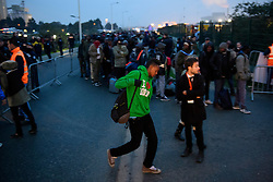"© Licensed to London News Pictures. 24/10/2016. Calais, France. A man wearing an ""I LOVE LONDON"" jumper. Thousand of migrant queue to board busses as the evacuation and demolition begins at the migrant camp in Calais, known as the 'Jungle'. French authorities have given an eviction order to thousands of refugees and migrants living at the makeshift living area of the French coast. Photo credit: Ben Cawthra/LNP"