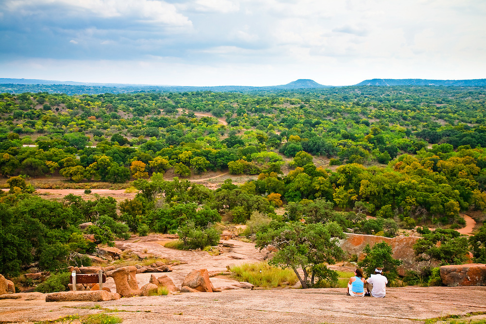 A couple takes in the view at Enchanted Rock State Park in the Texas Hill Country.